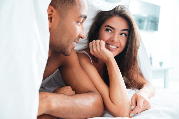 Smiling young couple lying under the coverlet in bed - Facts about dating a Scorpio Man