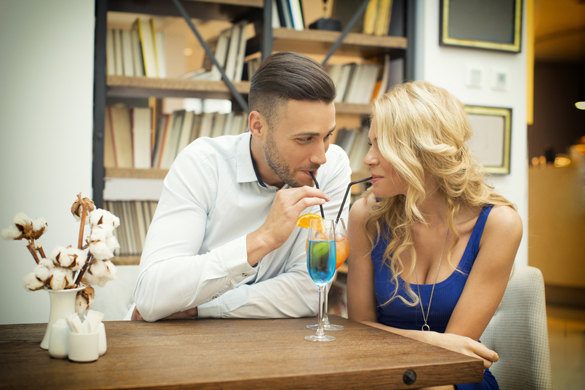 Beautiful couple drinking cocktail from the same glass - Get A Scorpio Man to Chase You