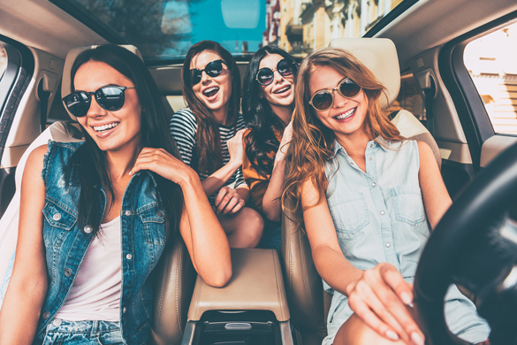 Four beautiful young cheerful women looking at camera with smile while sitting in car - What type of Woman does the Scorpio Man Prefer Physically