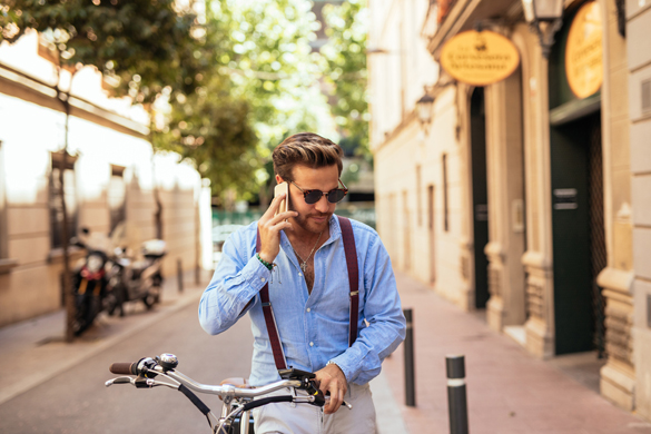 Handsome stylish man talking on the phone and driving a bike in the city - Does My Scorpio Man Miss Me When I'm not Around