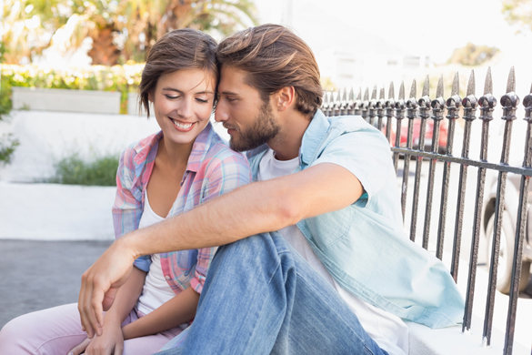 Happy couple sitting and cuddling on a sunny day in the city - How To Keep A Scorpio Man Once You Get Him