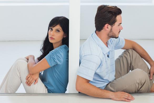 Sitting couple are separated by wall with woman looking at camera - Is It Possible To Get a Scorpio Man To Change His Mind