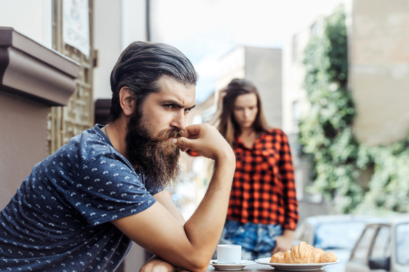 Unhappy man hipster with long beard and moustache has relationship difficulties with pretty girl in cafe outdoors - Why Scorpio Men Hate Being Compared to Other Men