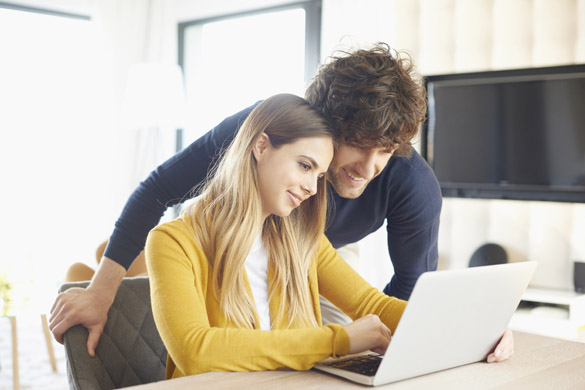 young couple using a laptop at home - What a Scorpio Man Does To Show You He Loves You